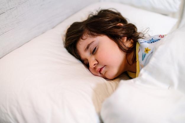 Dziecko śpiące W łóżku Z Zamkniętymi Oczami I Niewinną Twarzą, Ubrane W Piżamę I Białą Pościel Premium Zdjęcia