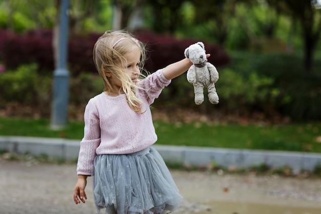 Dziecko Trzyma Brudnego Misia Plenerowego Premium Zdjęcia