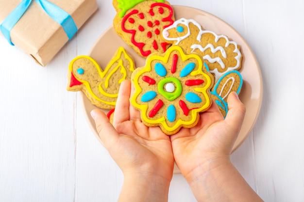Dziecko Trzyma Domowej Roboty Malowany Piernik (ciasteczko) Wśród Gałęzi Jodłowych I Prezenty Na Przyjęcie Urodzinowe Premium Zdjęcia