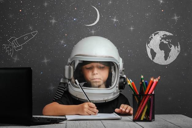 Dziecko Uczy Się Zdalnie W Szkole, Ubrane W Hełm Astronauty. Powrót Do Szkoły Premium Zdjęcia