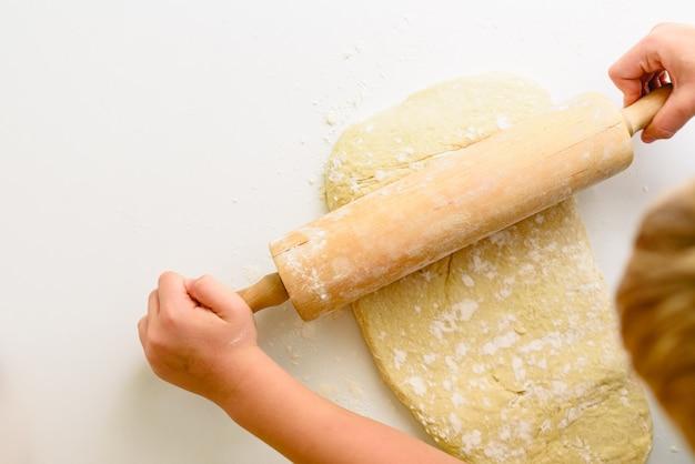 Dziecko ugniatając ciasto z pizzy, oglądane z góry. Premium Zdjęcia