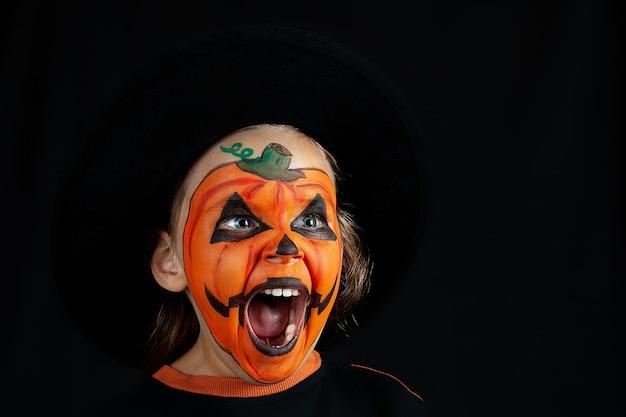 Dziecko W Czarnym Kapeluszu I Krzyczy Dyni Makijaż, Odizolowane. Premium Zdjęcia