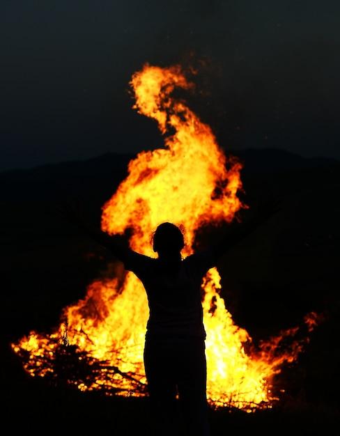 Dziecko W Ogniu Z Szeroko Otwartymi Ramionami Premium Zdjęcia