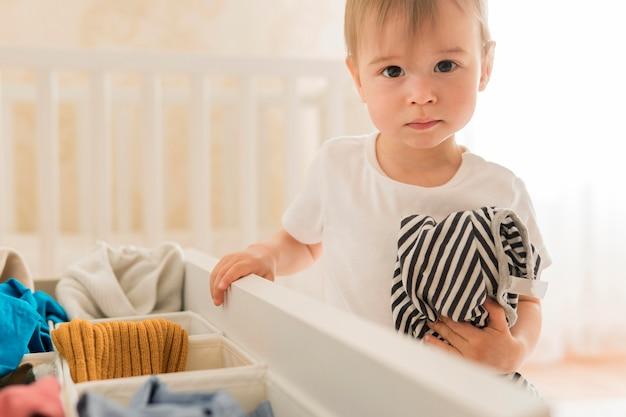 Dziecko W Połowie Strzału, Biorąc Ubrania Z Szuflady Darmowe Zdjęcia