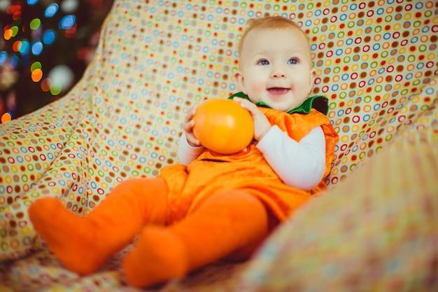 Dziecko W Pomarańczowym Garniturze Leży Na Krześle Darmowe Zdjęcia