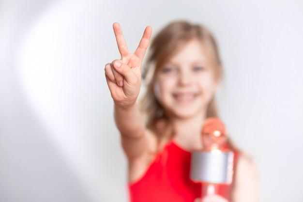 Dziecko W Wieku 7-8 Lat, Urocza Urocza Blondynka O Blond Włosach śpiewa W Urządzeniu, Mikrofon Bluetooth I Uśmiecha Się Na Szarej ścianie. Pokazuje Fajnie Dwoma Palcami Premium Zdjęcia