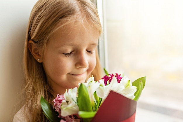 Dziecko W Wieku Szkolnym Wąchanie Bukiet Kwiatów Premium Zdjęcia