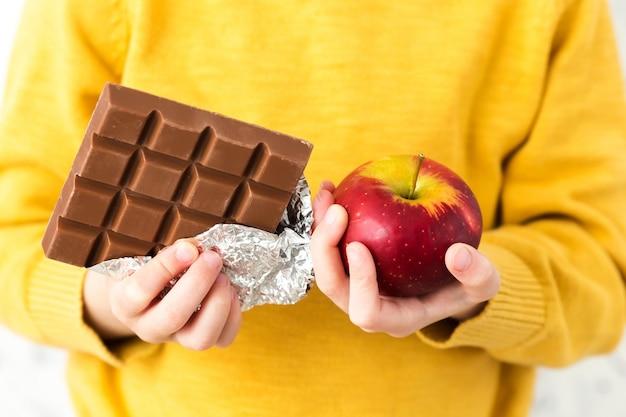 Dziecko W żółtym Swetrze Z Jabłkiem I Czekoladą. Premium Zdjęcia