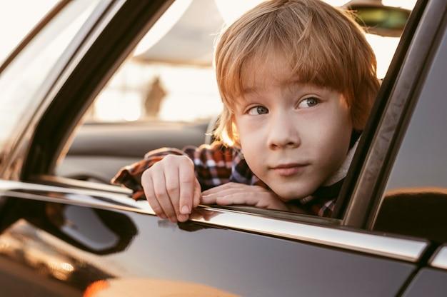 Dziecko Wyglądające Głową Przez Okno Samochodu Podczas Podróży Darmowe Zdjęcia