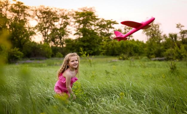 Dziecko wystrzeliwuje różowy samolot na tle lasu i wysokiej trawy. zabawa z różowym samolotem w różowym garniturze Premium Zdjęcia