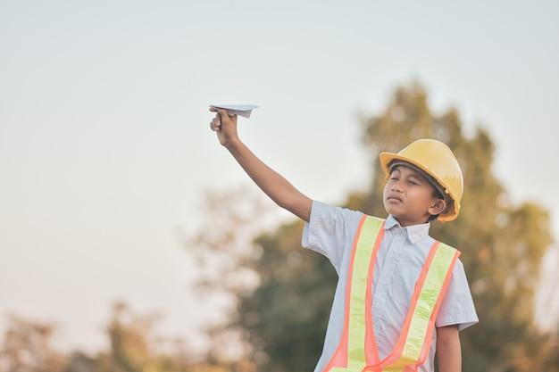 Dziecko Z żółtym Kask I Papierowy Samolot Premium Zdjęcia
