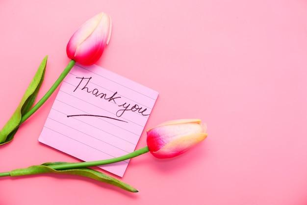 Dziękuję Wiadomość Na Karteczce Z Kwiatem Tulipana Na Różowym Tle. Premium Zdjęcia