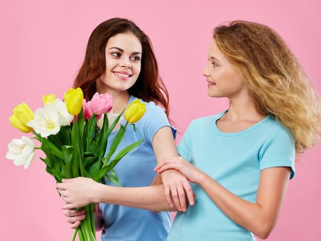 Dzień Matki, Młoda Kobieta Z Dzieckiem Pozuje W Studio Z Kwiatami, Prezent Na Dzień Kobiet I Dzień Matki Premium Zdjęcia