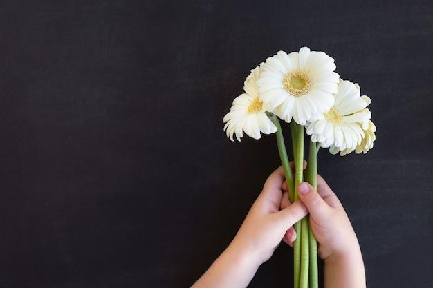 Dzień Nauczyciela. Dziecko Trzymając Się Za Ręce Bukiet Kwiatów Na Tablicy Premium Zdjęcia