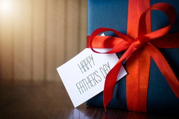 Dzień ojca. pakiet prezent owinięty niebieskim papierze i liny z czerwoną wstążką na drewnianym tle Premium Zdjęcia