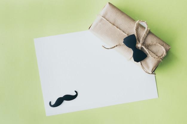 Dzień Ojca. Pakiet Prezent Owinięty Papierem I Liną Z Ozdobną Muszką Na Zielonym Tle. Copyspace Premium Zdjęcia