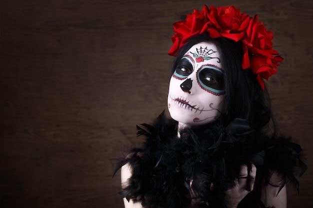 Dzień śmierci. Halloween Młoda Kobieta W Dzień Sztuki Martwej Maski Czaszki Sztuki Twarzy I Wzrosła. Ciemne Tło Premium Zdjęcia