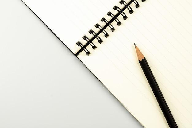 Dzienniczek książka i ołówek na białym biurka tle z kopii przestrzenią Premium Zdjęcia