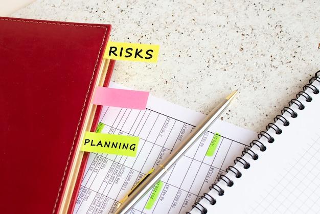 Dziennik Biznesowy Z Kolorowymi Zakładkami Z Napisami Leży Na Wykresach Finansowych Na Biurku. Premium Zdjęcia