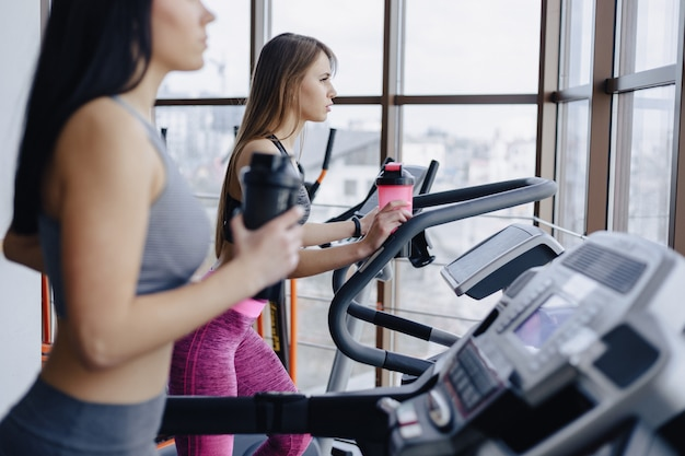Dziewczęta na siłowni trenują na bieżniach i piją wodę, uśmiechając się Premium Zdjęcia