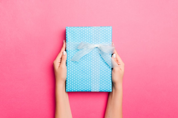 Dziewczyn Ręki Trzyma Rzemieślniczego Papierowego Prezenta Pudełko Z Prezentem Dla Bożych Narodzeń Lub Innego Wakacje Na Różowym Tle Premium Zdjęcia