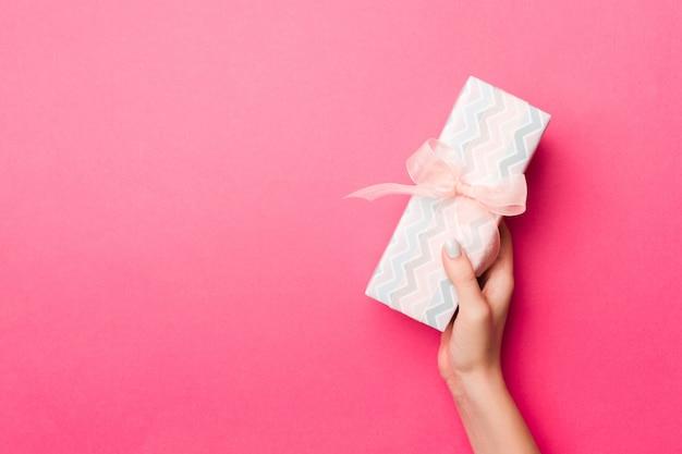 Dziewczyn ręki trzyma rzemiosło tapetują papierowego prezenta pudełko z teraźniejszością dla bożych narodzeń lub innego wakacje na różowym tle, odgórny widok z odbitkowym przestrzenią Premium Zdjęcia