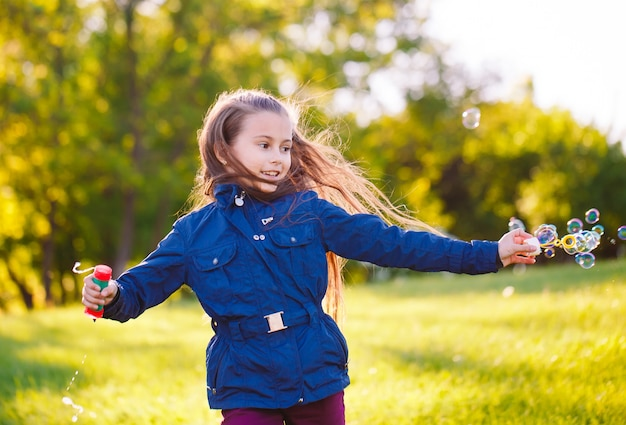 Dziewczyna biegnie i bawi się bańkami mydlanymi. Premium Zdjęcia