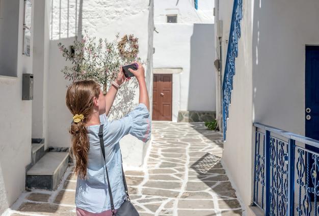 Dziewczyna Bierze Fotografię Grecka Nieociosana Architektura Na Smartphone Premium Zdjęcia