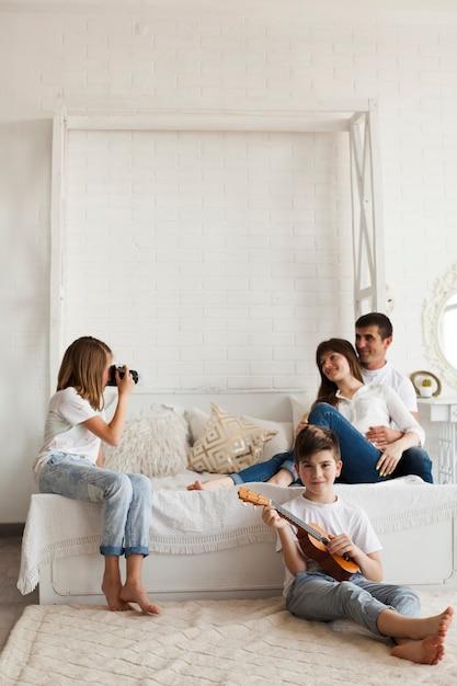 Dziewczyna bierze fotografię jej rodzice i jej brat bawić się ukulele w domu Darmowe Zdjęcia