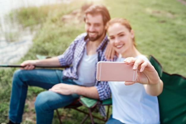 Dziewczyna Bierze Selfie Z Siebie I Męża. Patrzą Na Telefon I Uśmiechają Się. Facet Trzyma Koniec Wędki. Ludzie Siedzą Na Składanych Krzesłach. Premium Zdjęcia