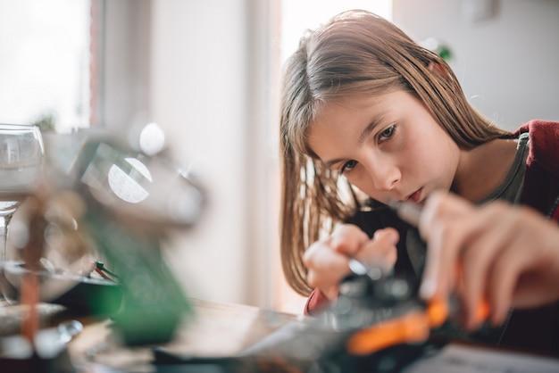 Dziewczyna buduje robota w domu Premium Zdjęcia