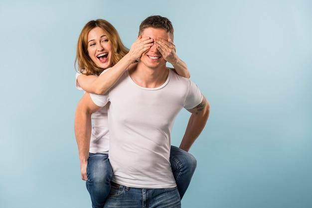Dziewczyna cieszy się piggyback przejażdżkę na jej chłopaku przeciw błękitnemu tłu Darmowe Zdjęcia