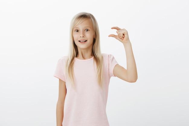 Dziewczyna Czuje Się Optymistycznie I Podekscytowana, Dzieląc Się Wrażeniami Po Wizycie W Zoo. śliczna Blond Córka W Różowym T-shircie, Unosząca Rękę I Nad Szarą ścianą Kształtująca Drobiazg Z Pełnym Podziwu Wyrazem Twarzy Darmowe Zdjęcia