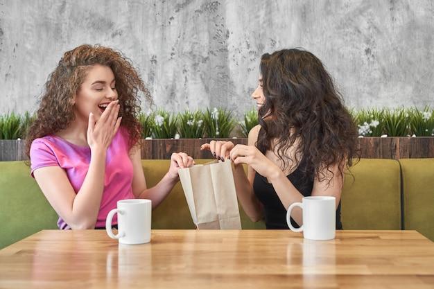Dziewczyna Daje Teraźniejszości Zdziwiony Przyjaciel W Kawiarni. Premium Zdjęcia