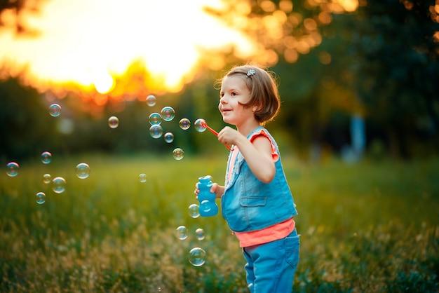 Dziewczyna Dmuchanie Baniek Mydlanych Na Zewnątrz Premium Zdjęcia