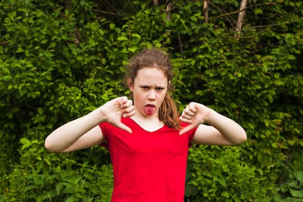 Dziewczyna dokucza z wystającym jęzorem patrzeje kamerę w parku Darmowe Zdjęcia