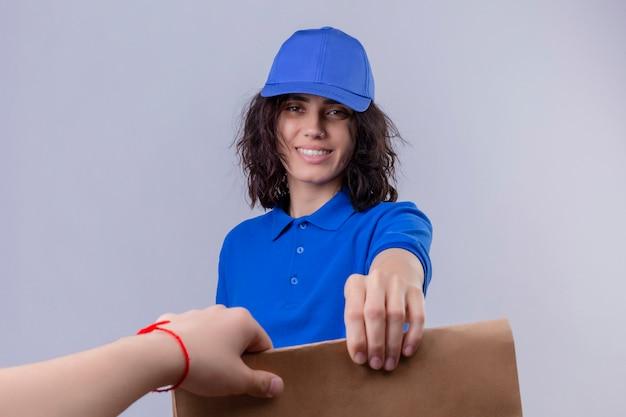 Dziewczyna Dostawy W Niebieskim Mundurze I Czapce, Dając Pakiet Papieru Do Klienta Uśmiechnięty Przyjazny Na Pojedyncze Białe Miejsca Darmowe Zdjęcia