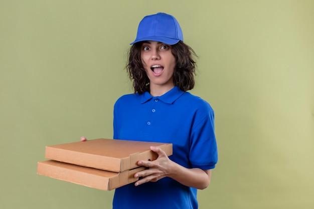Dziewczyna Dostawy W Niebieskim Mundurze I Czapce Trzymająca Pudełka Po Pizzy Wyglądająca Radośnie Pozytywnie I Szczęśliwie, Uśmiechnięta Wesoło, Stojąca Na Odizolowanej Zielonej Przestrzeni Darmowe Zdjęcia