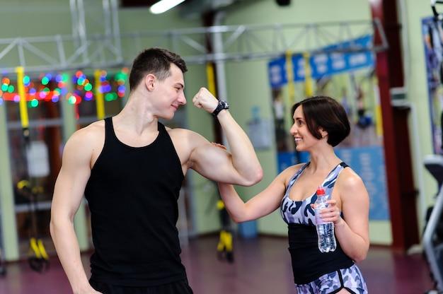 Dziewczyna Dotyka Mięśni Faceta Na Siłowni. Premium Zdjęcia
