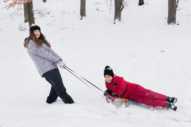 Dziewczyna i chłopiec ma zabawy saneczki jedziemy na śnieżnym krajobrazie Darmowe Zdjęcia