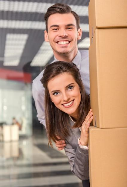 Dziewczyna i mężczyzna wyglądają zza pudełka i uśmiechają się. Premium Zdjęcia