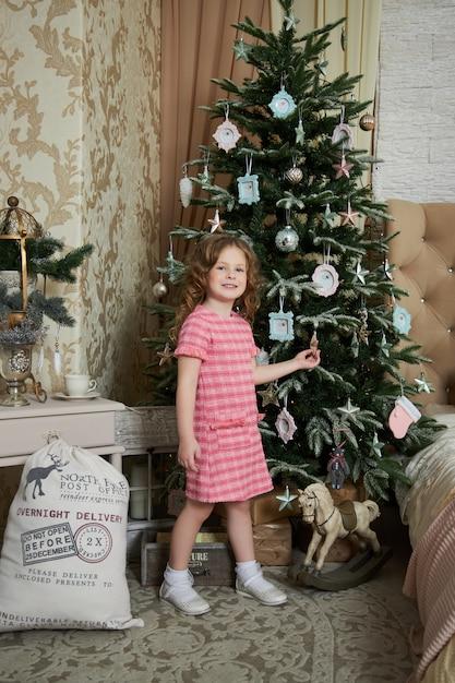 Dziewczyna I Poranek Bożonarodzeniowy, Dziecko Pozujące Do Wnętrza Choinki Premium Zdjęcia