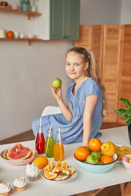 Dziewczyna Je Owoce Na Stole Pełnym Jedzenia Premium Zdjęcia
