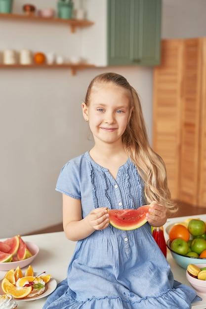 Dziewczyna Je Owoce W Kuchni Premium Zdjęcia