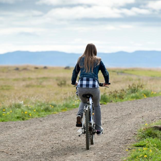 Dziewczyna Jeździecki Bicykl Na Niebrukowanej Wiejskiej Drodze Premium Zdjęcia