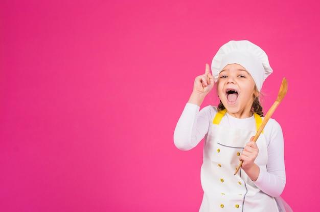 Dziewczyna kucharz z kopyścią pokazuje palec wskazującego Darmowe Zdjęcia