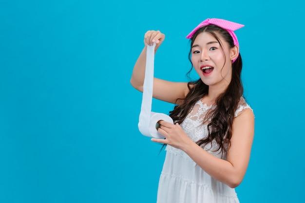 Dziewczyna Ma Na Sobie Białą Piżamę Trzymając Papier Rolltissue W Dłoni Na Niebiesko. Darmowe Zdjęcia
