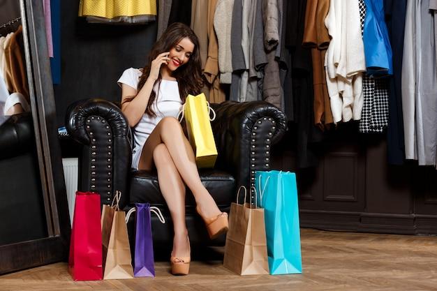 Dziewczyna Mówi Na Telefon, Siedząc W Centrum Handlowym Z Zakupami. Darmowe Zdjęcia