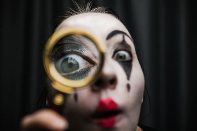 Dziewczyna na obrazie mima trzyma lupę. Premium Zdjęcia
