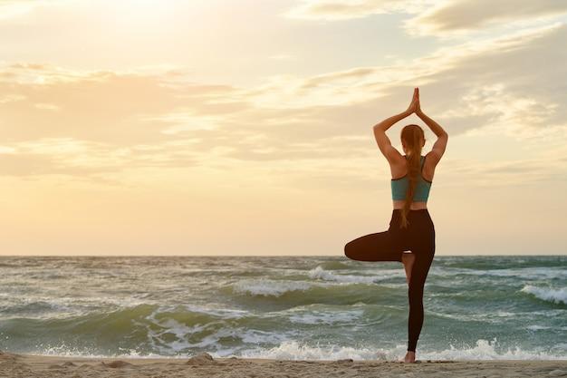 Dziewczyna Na Plaży Praktykujących Jogę. Widok Z Tyłu. Piękne światło Słoneczne Premium Zdjęcia